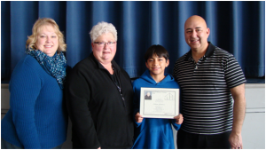 Adrian Gutierrez, 6th grader, receiving his 100th Mass Certificate with (from L-R) Ms. Karen Suty (Principal), and his parents, Mrs. Geralyn Gutierrez and Mr. Michael Gutierrez.