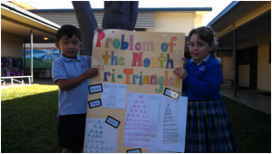 Our First Grade students with their Problem of the Month posters.